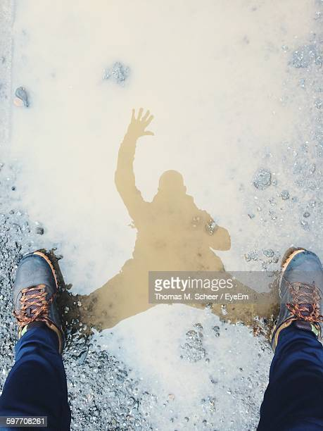 Low Section Of Man With Reflection On Puddle