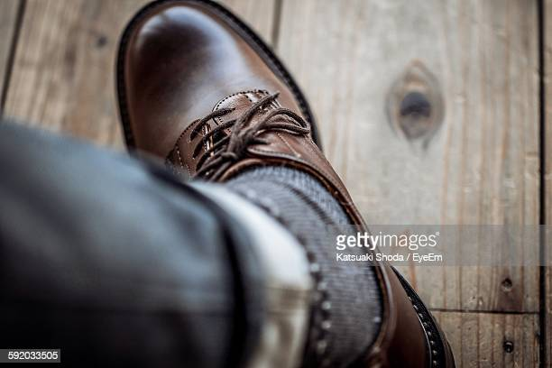 Low Section Of Man With Shoe On Wooden Floor