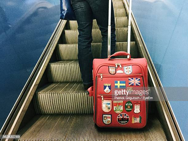 Low Section Of Man With Suitcase In Escalator