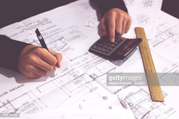 Low Section Of Man Working On Blueprints
