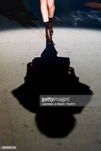 Low Section Of Model On Catwalk At Fashion Show With Shadow