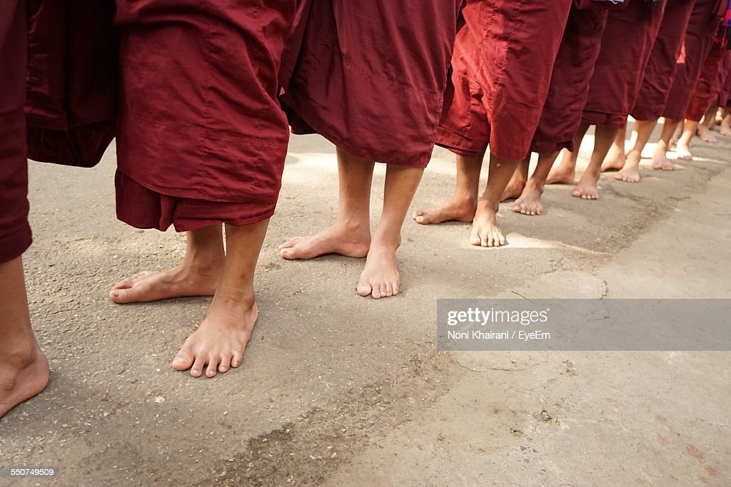Low Section Of Monks Standing In Line On Street