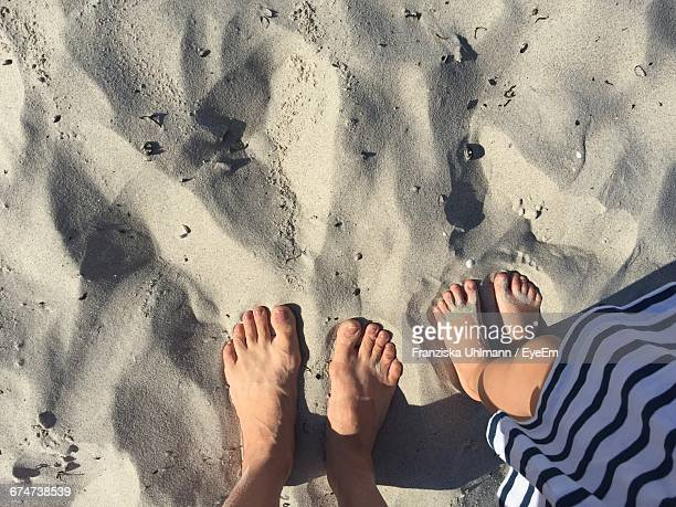 Low Section Of Mother And Child Standing On Sand During Sunny Day