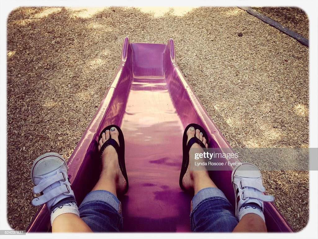Low Section of Mother With Child On Slide At Amusement Park