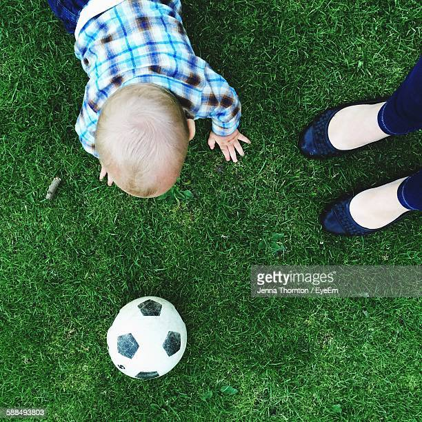 Low Section Of Mother With Son Playing Soccer On Grassy Field