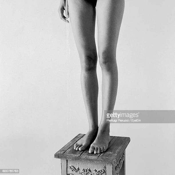 Low Section Of Naked Woman Standing On Wooden Stool Against White Background