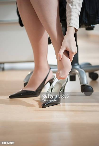 Low section of office worker massaging foot