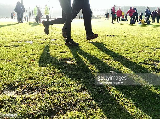 Low Section Of People Running On Grassy Field
