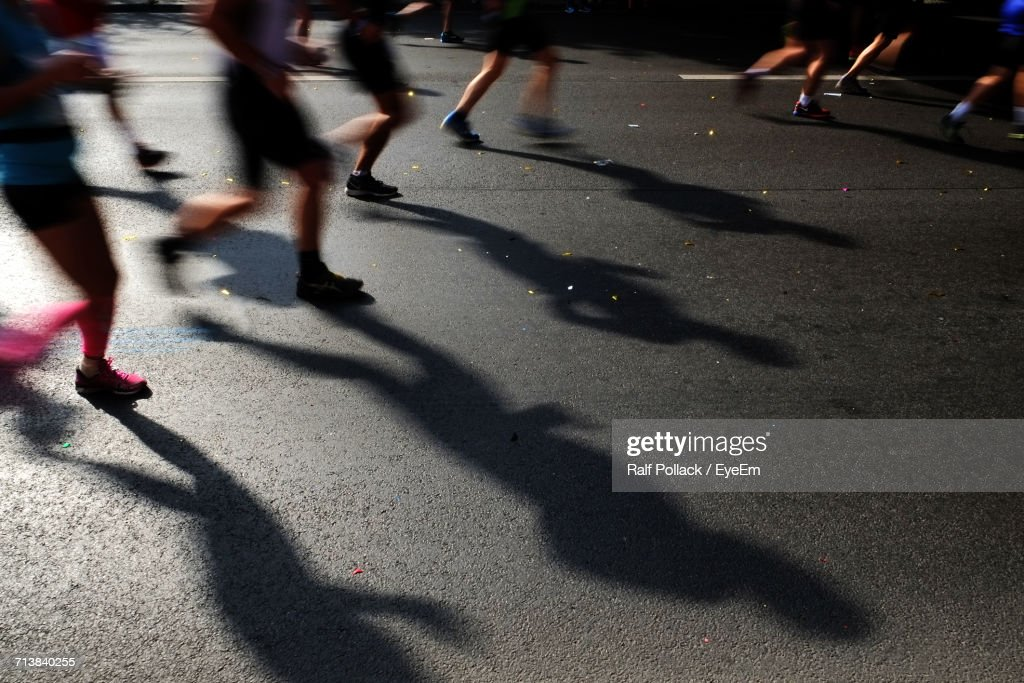 Low Section Of People Running On Street During Marathon : Stock Photo