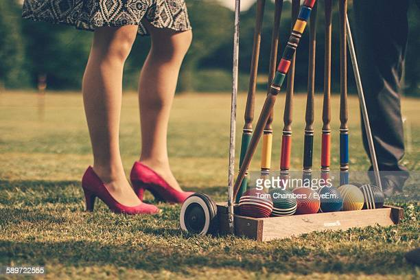 Low Section Of People Standing By Croquet Set On Grassy Field