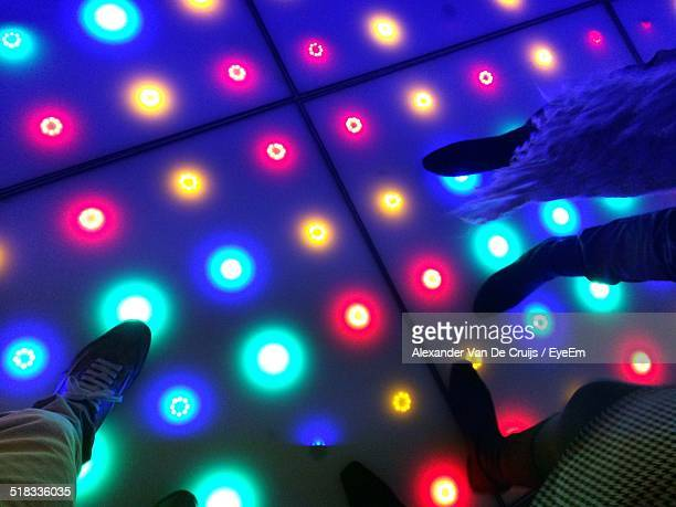 Low Section Of People Standing On Illuminated Dance Floor