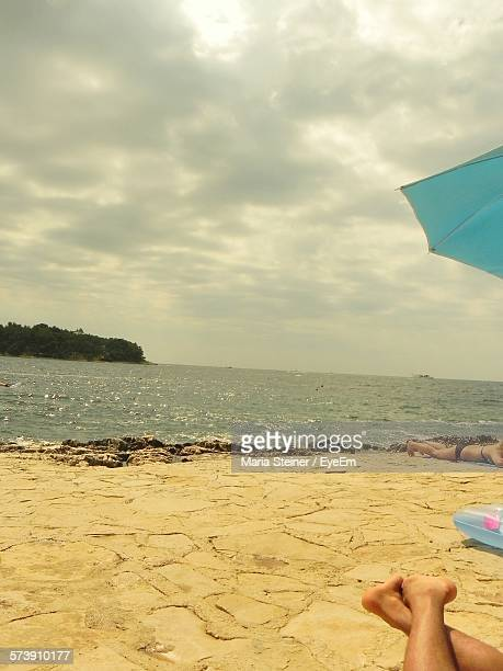 Low Section Of People Sunbathing On Sand At Beach Against Sky