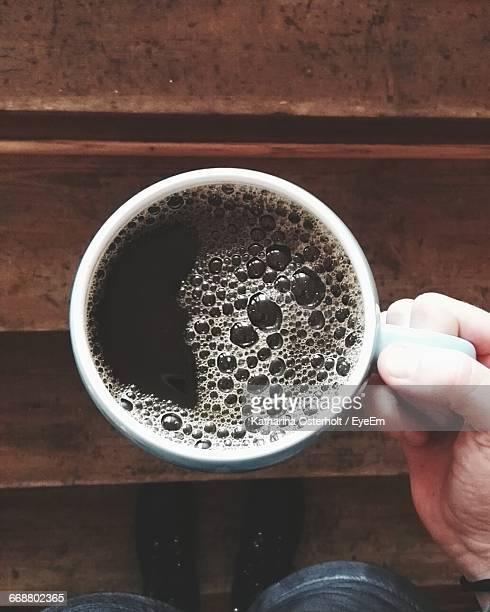 Low Section Of Person Holding Black Coffee On Steps