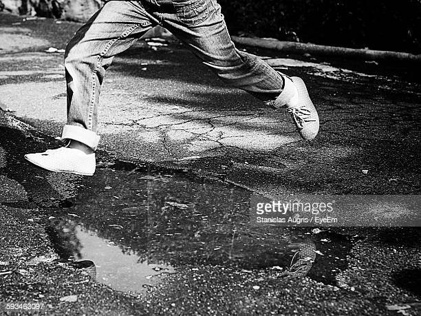Low Section Of Person Jumping Over Puddle On Street
