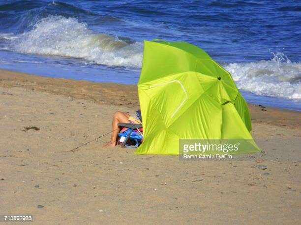 Low Section Of Person Relaxing At Beach During Sunny Day