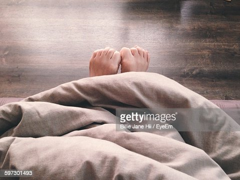 Low Section Of Person Relaxing On Bed At Home