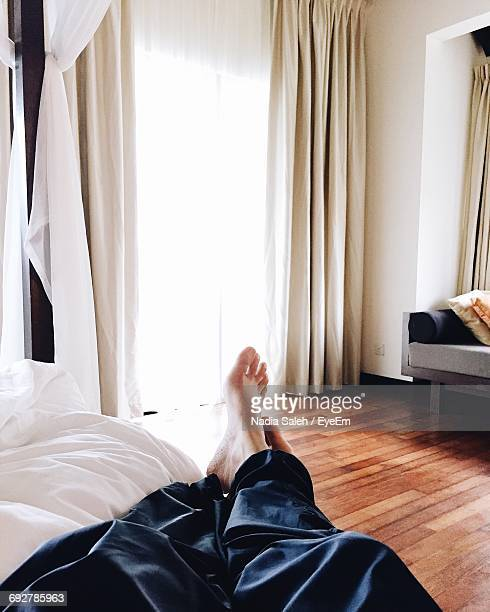 Low Section Of Person Resting On Bed At Home