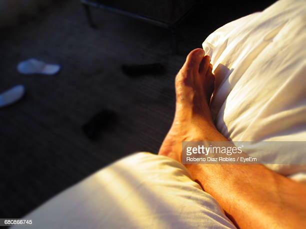 Low Section Of Person Resting On Bed At Morning