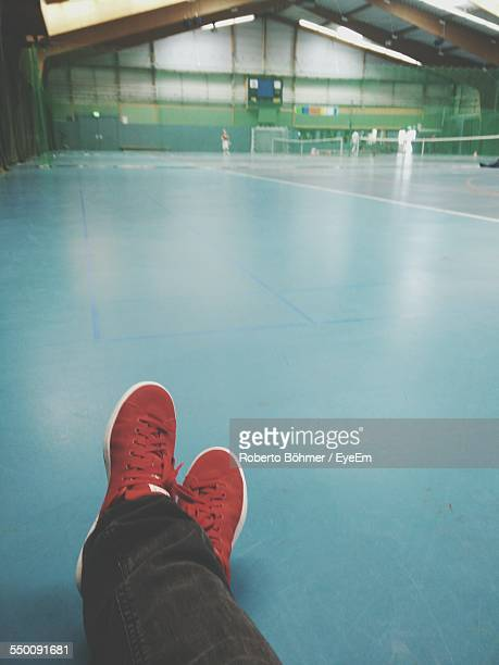 Low Section Of Person Sitting On Badminton Court