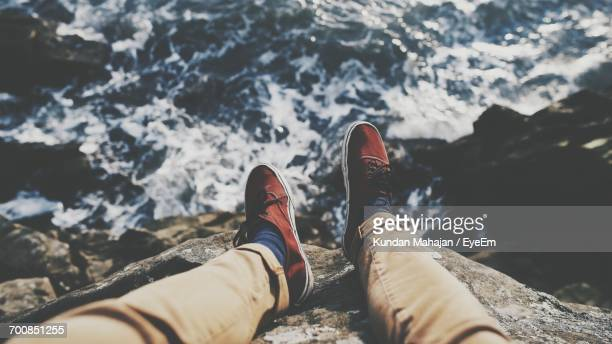 Low Section Of Person Sitting On Beach Cliff