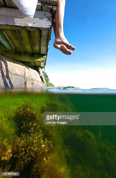 Low section of person sitting on jetty