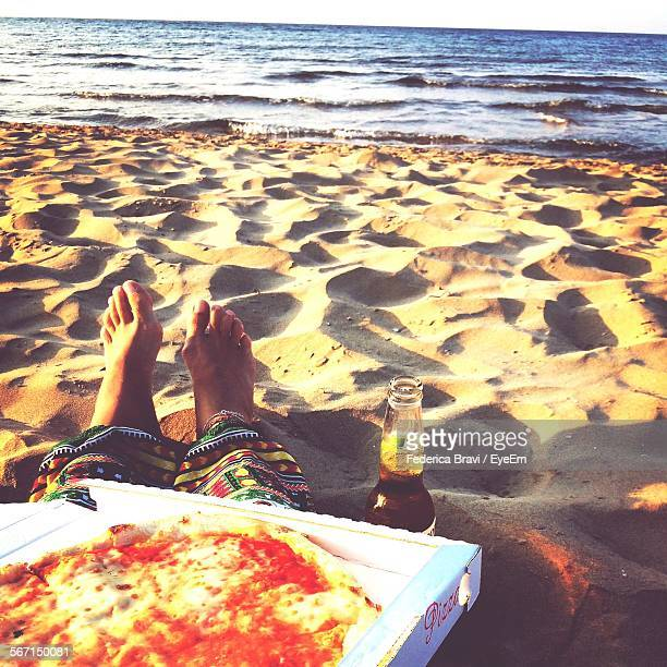 Low Section Of Person Sitting On Sandy Beach With Pizza And Beer Bottle