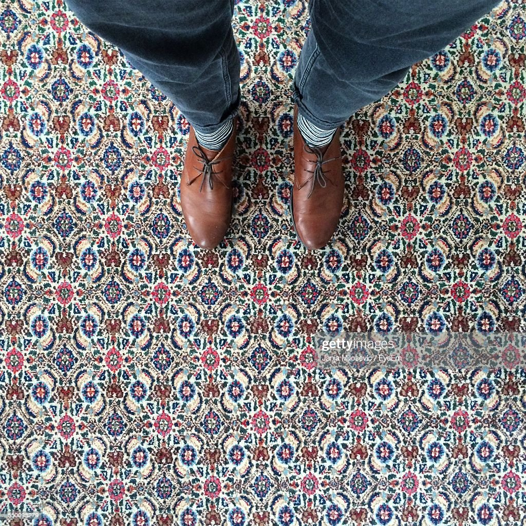 Low Section Of Person Standing On Carpet