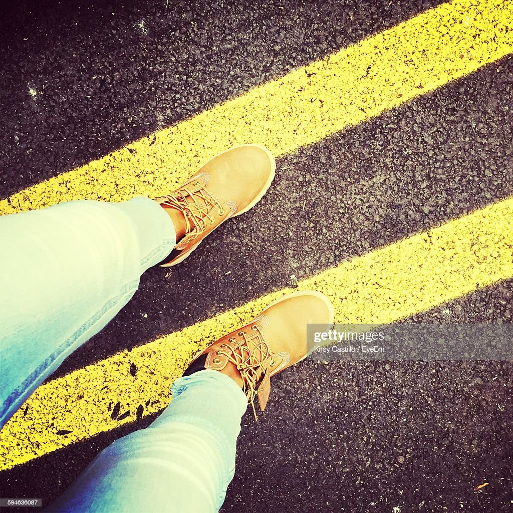 Low Section Of Person Standing On Double Yellow Line