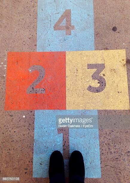 Low Section Of Person Standing On Hopscotch At Street