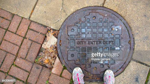 Low section of person standing on manhole cover at the city of Cleveland, Ohio