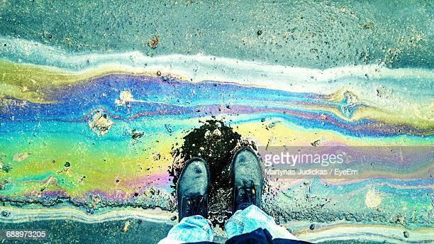 Low Section Of Person Standing On Oil Spill At Street During Monsoon