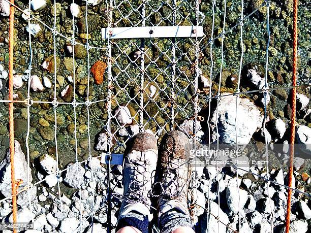 Low Section Of Person Standing On Rope Bridge Over Stream