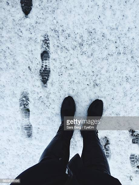 Low Section Of Person Standing On Snowcapped Field During Winter