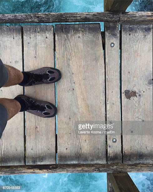 Low Section Of Person Standing On Wooden Jetty
