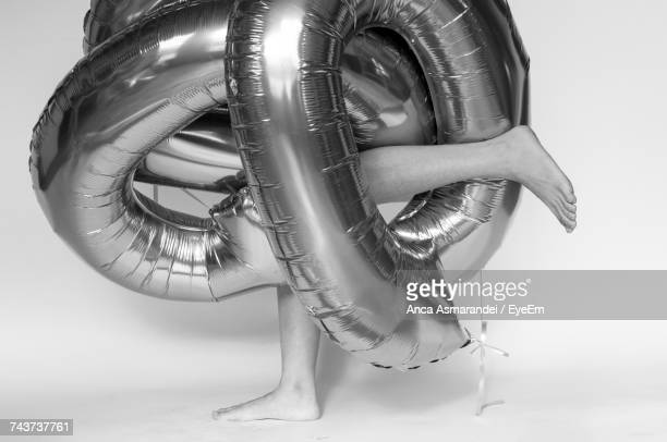 Low Section Of Person Wearing Inflatable Ring Against White Background