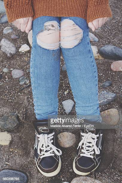 Low Section Of Person Wearing Torn Jeans On Street