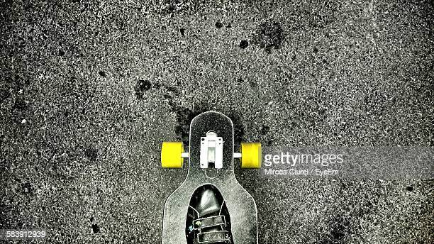 Low Section Of Person With Skateboard On Road