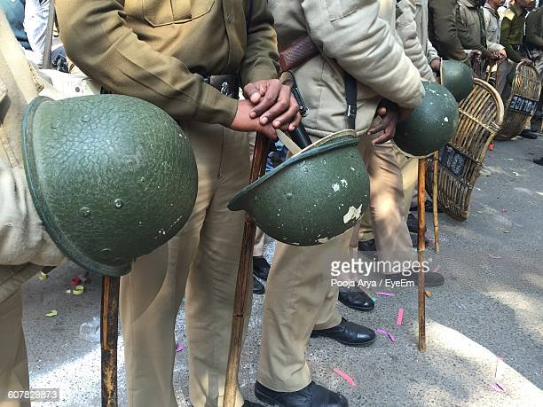 Low Section Of Police Holding Helmets While Standing On Street