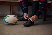 Low section of rugby player tying shoes while sitting on bench