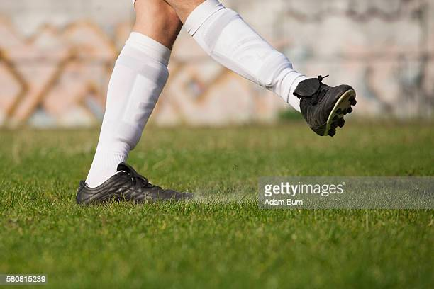 Low section of soccer player kicking on grassy field