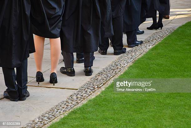 Low Section Of Students Standing By Grassy Field In University