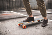 low section of stylish man in leather shoes with longboard