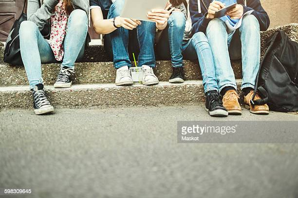 Low section of teenagers using digital table on steps