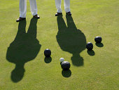 Low Section of Two Men Standing on a Bowling Green and a Group of Bowling Balls