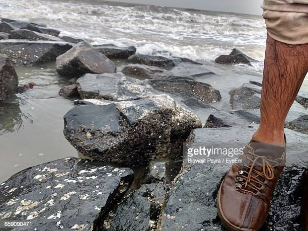 Low Section Of Wet Man Standing On Rock Against Sea
