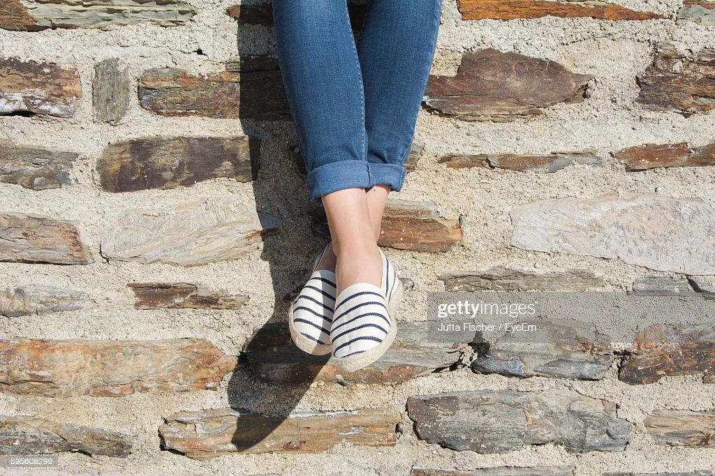 Low Section Of Woman Against Stone Wall
