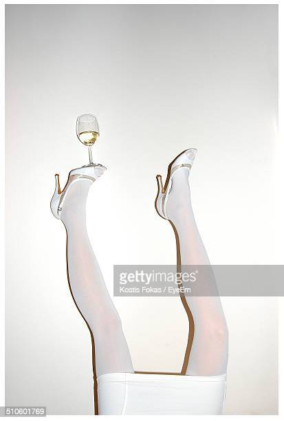 Low section of woman balancing wine glass