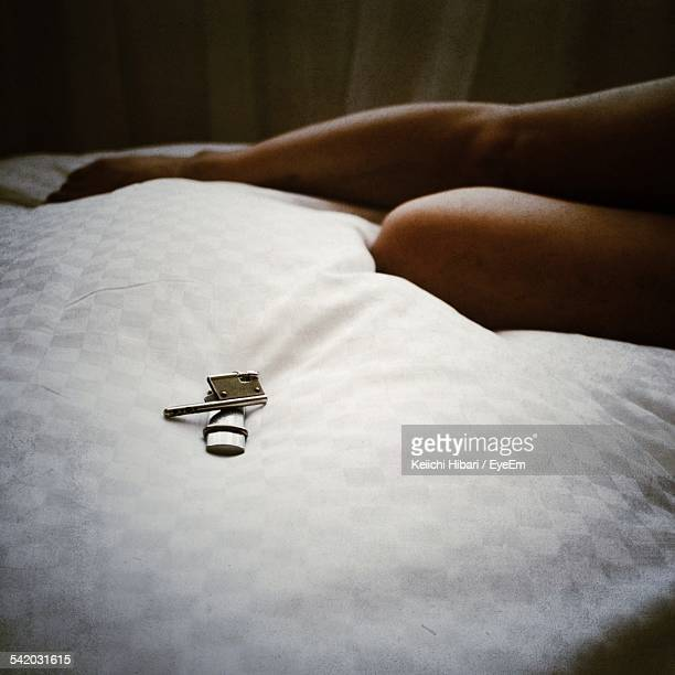 Low Section Of Woman By Key On Bed