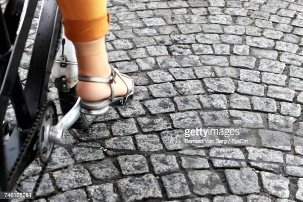 Low Section Of Woman Cycling On Cobbled Street
