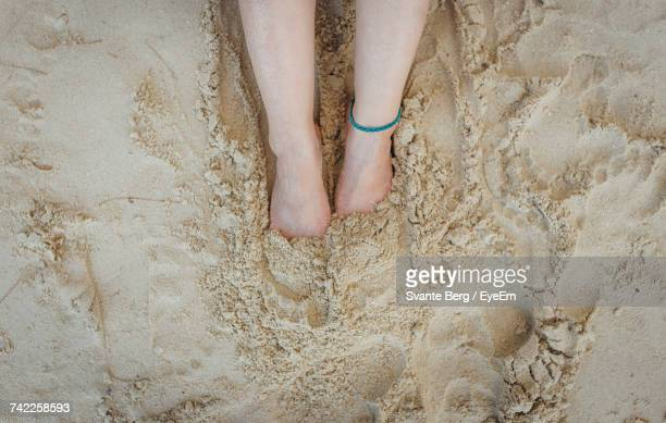 Low Section Of Woman Feet In Sand